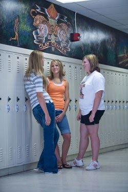 Teenage Girls Talking While Leaning Against White School Lockers